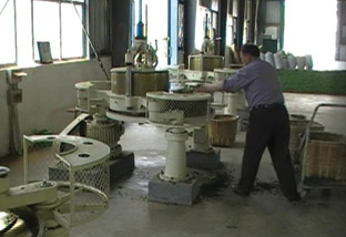 Well dressed worker putting wilted tea leaves into the rolling machine