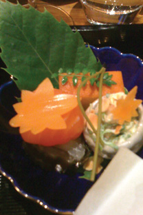 Arashimaya appetizers consisting of a small rolled seabass with konbu seaweed, crunchy bitter cabbage coleslaw, a sweet egg omelette Tamago, and a little smoked salmon ball covering the most intense sunset-orange, runny egg yolk.