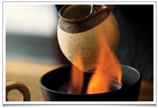 'Kao Cha' - a Dai ethnic minority's tea ritual in Yunnan.  The pu erh tea is placed in the small clay urn and heated over an open flame.  When there is a toasty aroma, the urn is removed from the flame and hot water poured into it.  When the bubbling subsides, the tea is ready to be served.