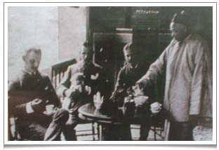 Western officials enjoying a cup of tea at a Chinese teahouse.  Note that the gentleman on the left is holding a Western cup and saucer whereas on the table on the right there is a Chinese gaiwan tea cup.